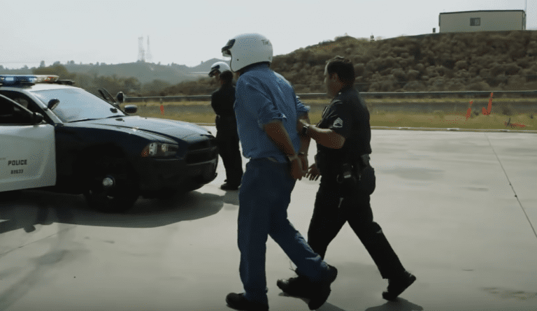 Jay Leno and Tim Allen end up in the back of police cruiser after a burnout competition