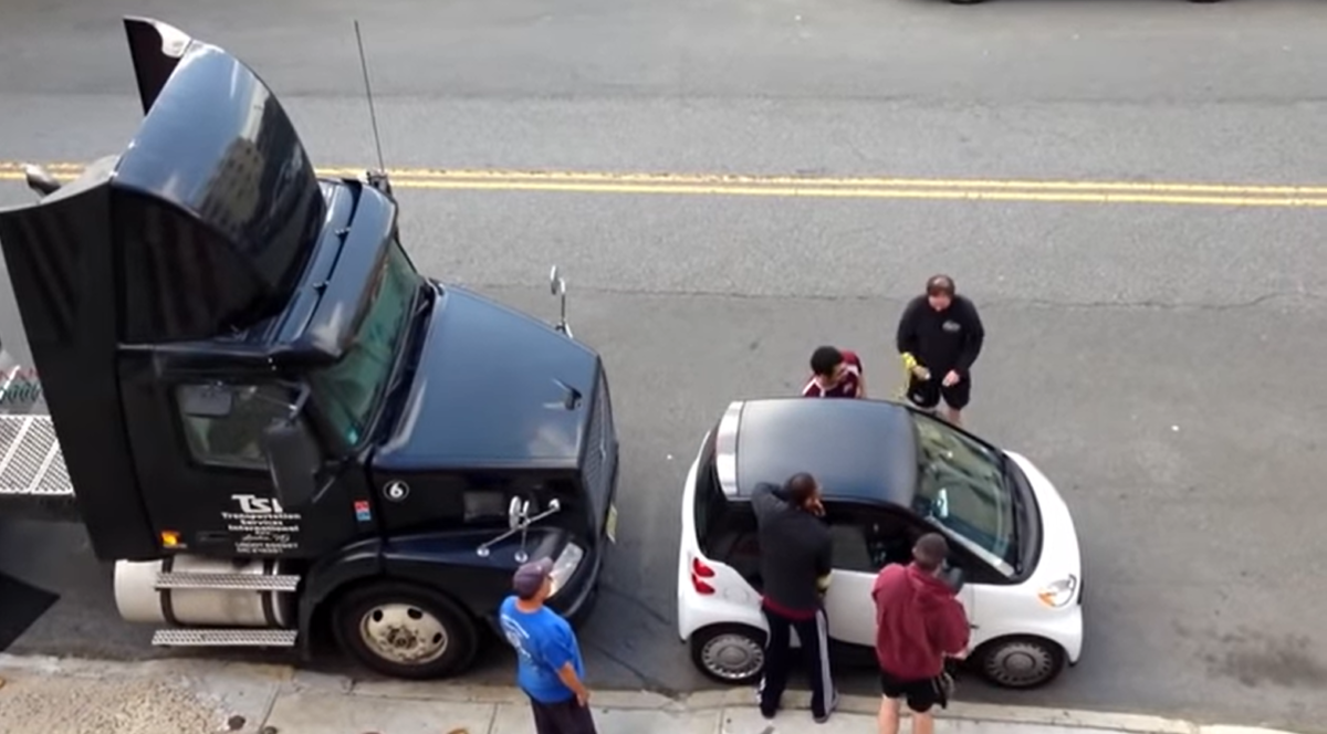5 guys lift a car to help a stranded semi