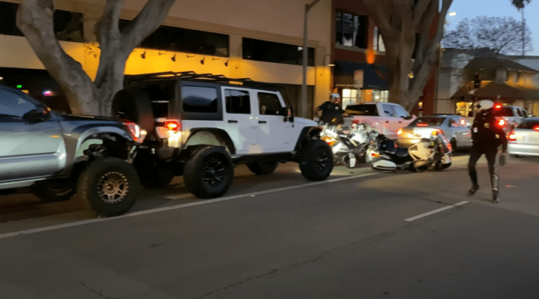 A truck pushes a Jeep into some motorcycle cops