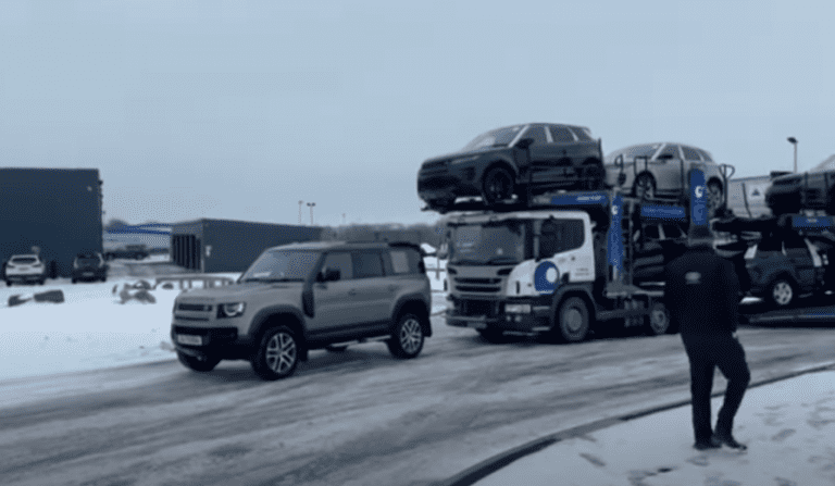 A Land Rover Defender pulls a 7 Car Transporter stuck on ice