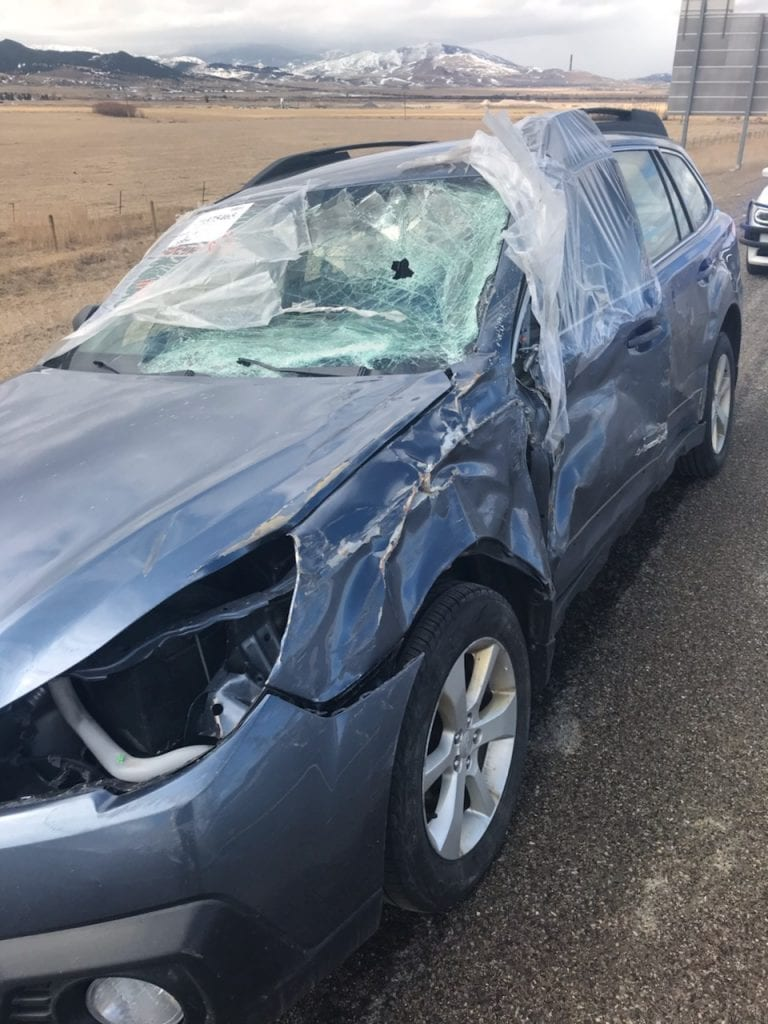 Guy drives his wrecked Subaru Outback while wearing safety glasses